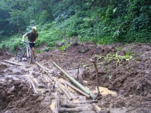 Seorang turis sedang melewati jalan yang tertimbun material longsor